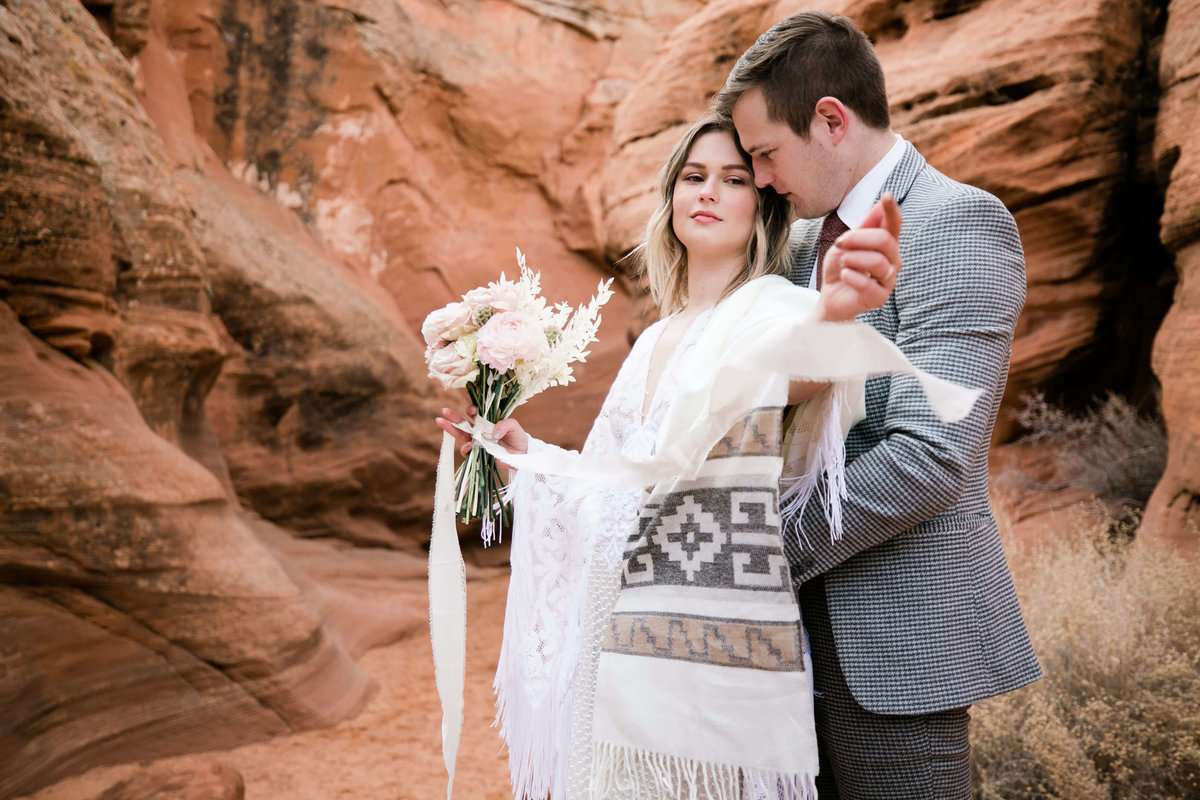 During their arizona elopement the bride plays with the ribbon on her bouquet..