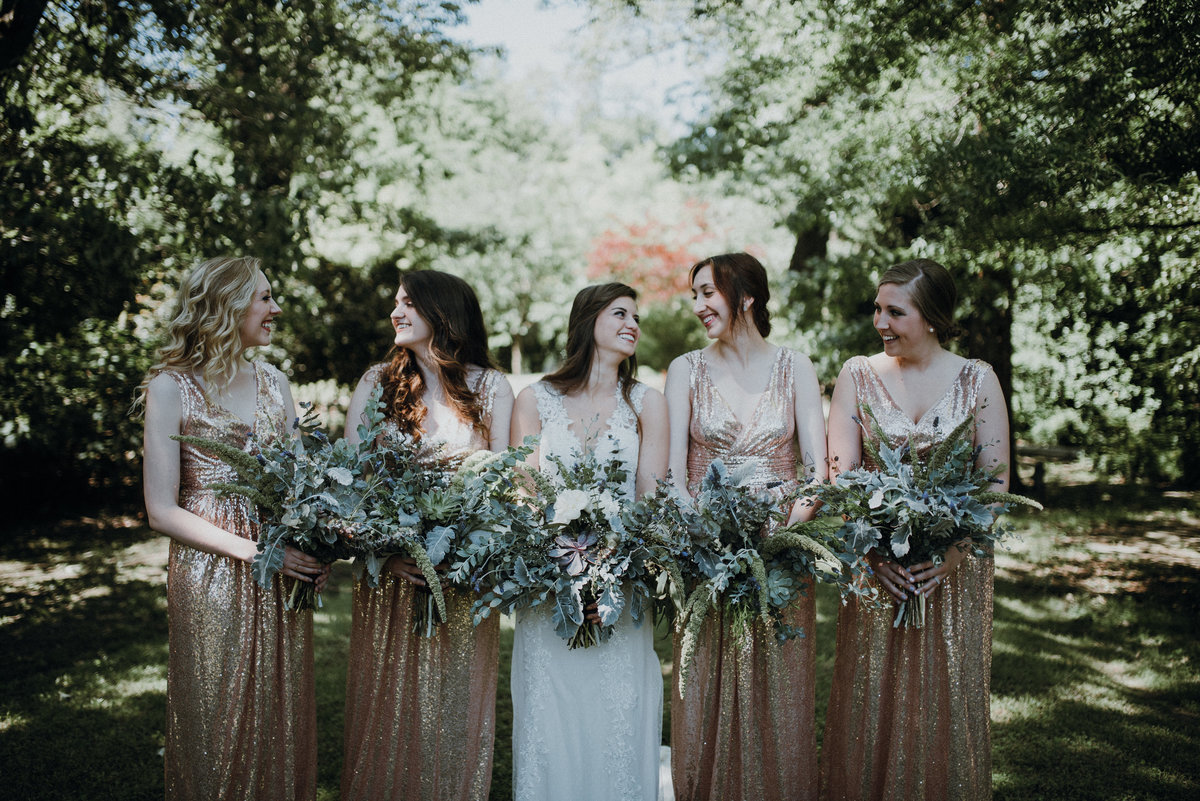 Bride and her bridesmaids laughing before their gorgeous estate wedding in Arkansas