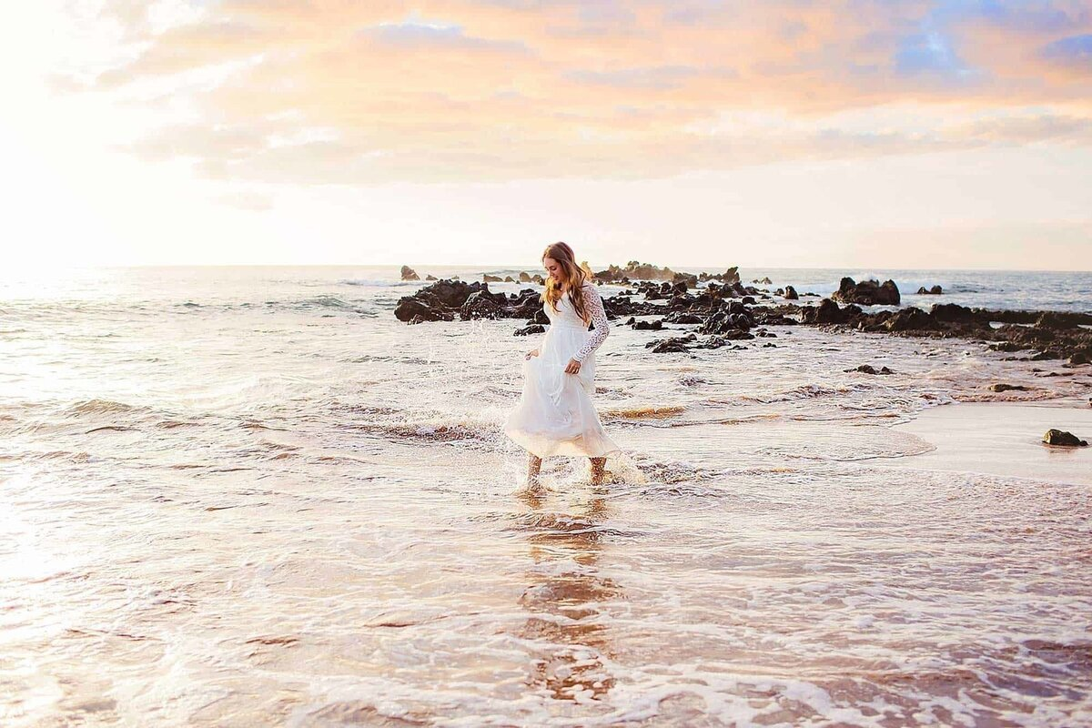 Bride holds her gown and tiptoes through the water on the shoreline after her beach elopement on Maui