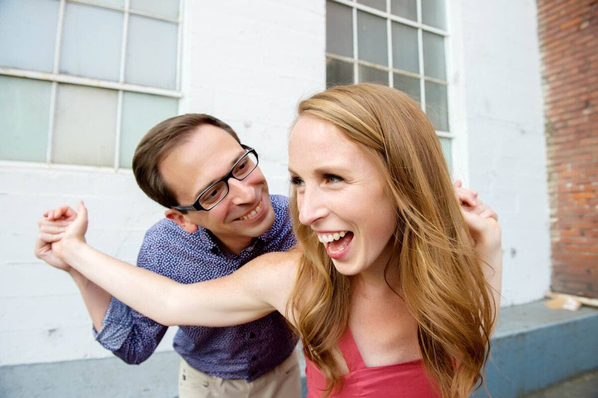 a fun couple pulls each others arms and laughs during their engagement photos
