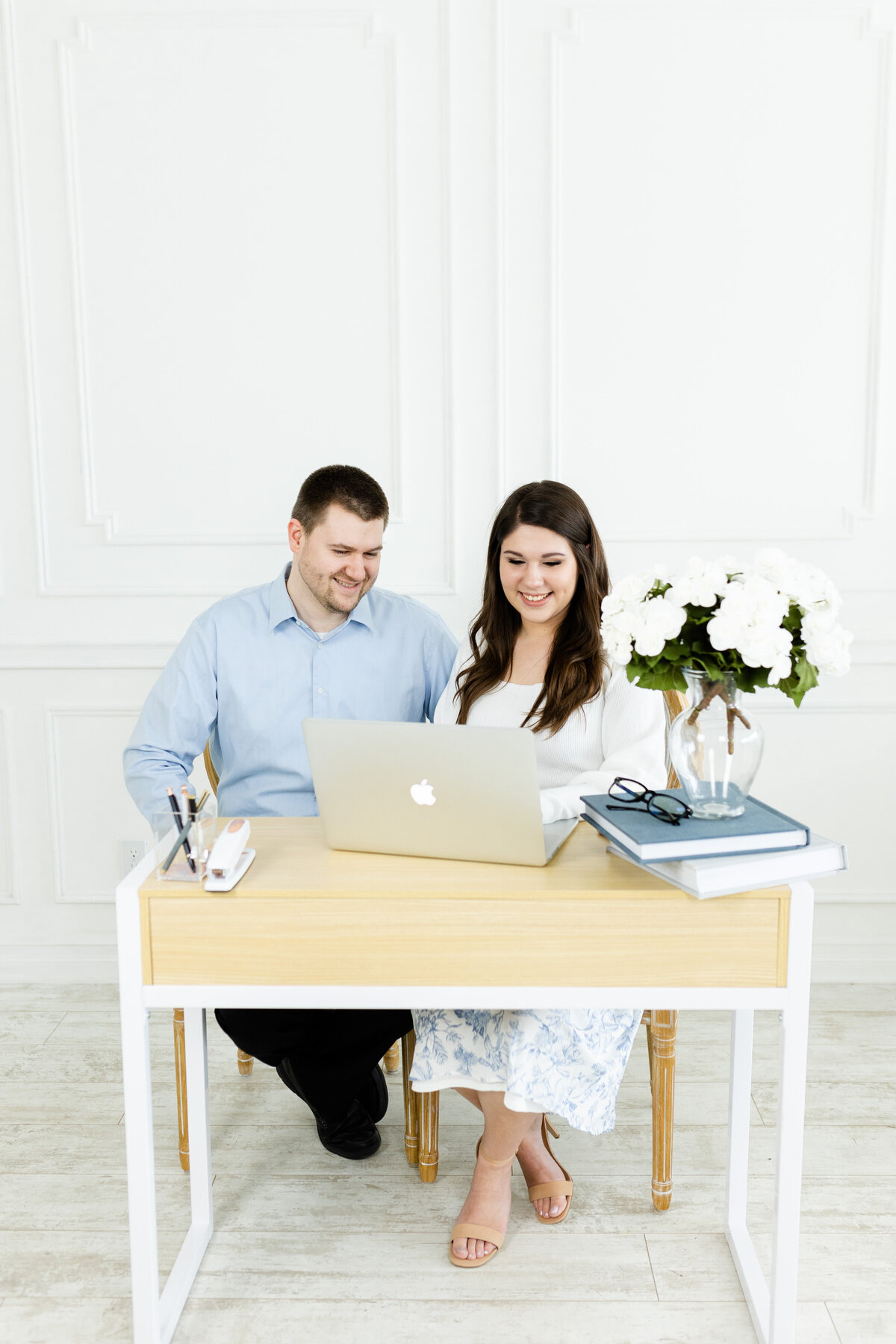 husband and wife sitting at desk for brand photos