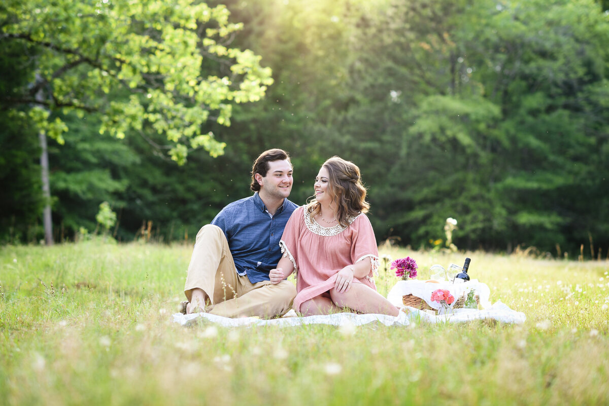 Beautiful Mississippi Engagement Photography: couple looks at each other while enjoying wine at engagement picnic