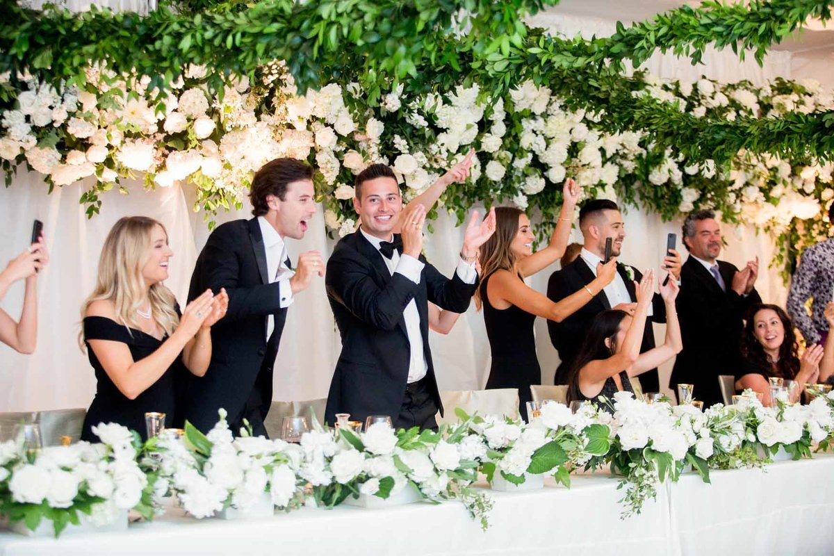 Wedding party behind head table with white floral installation
