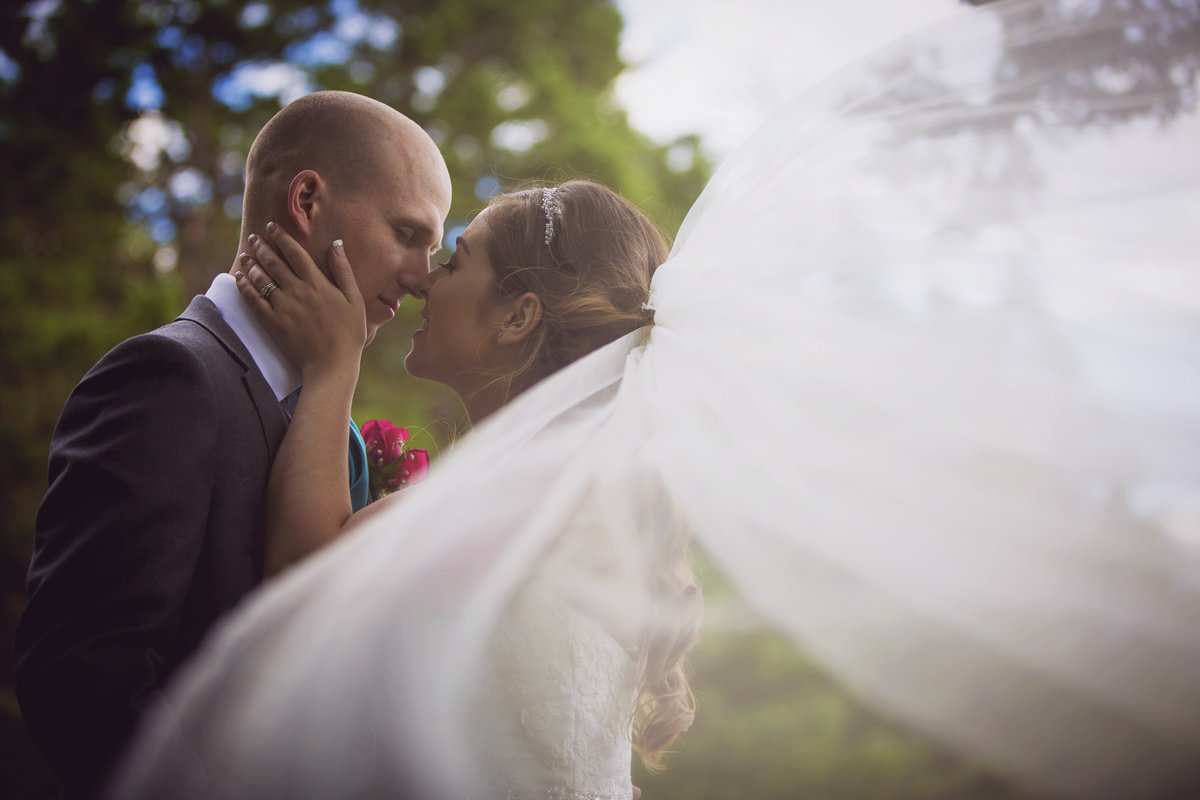 Bride and Groom kiss while veil blows in the wind. Artistic wedding photo with veil.