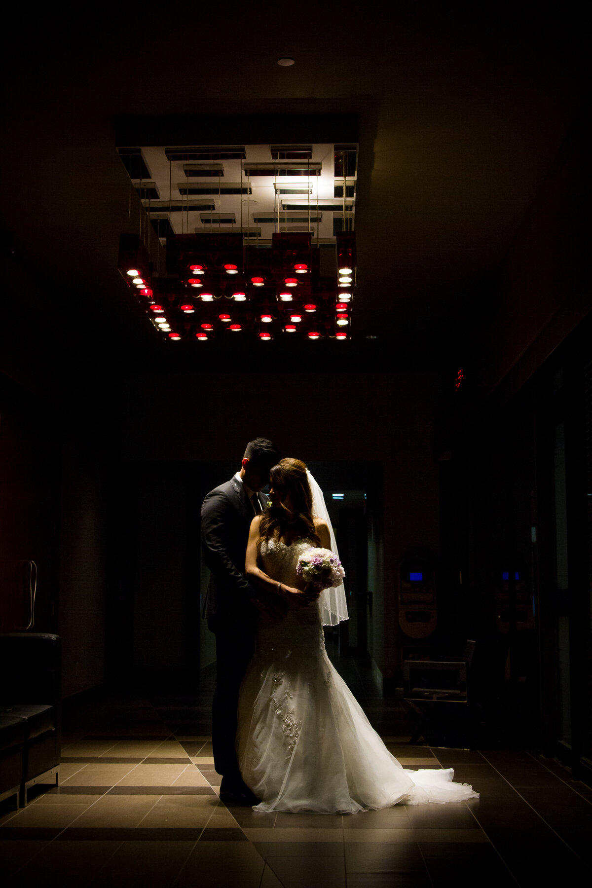 Dark lit wedding photo of couple during their first dance.