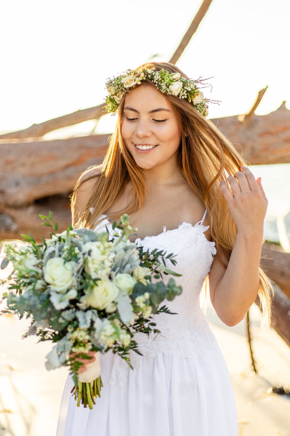 Bride in white and green flower crown sweeps long hair out of her face as she looks at her bridal bouquet on a beach in St. Petersburg, Florida