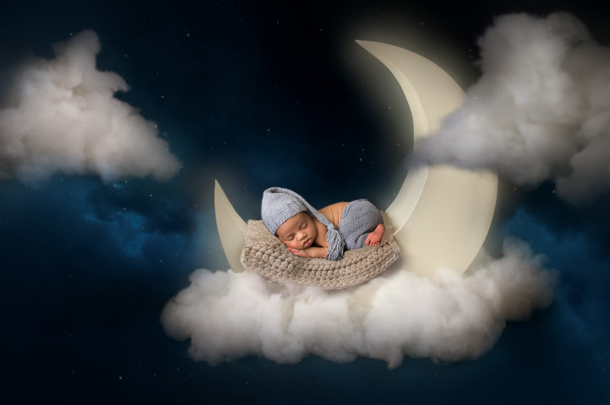 Little boy lying on a moon sleeping