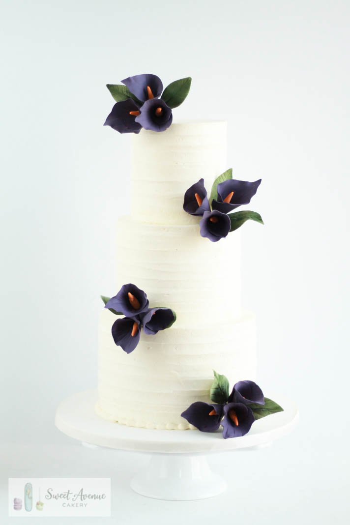 striped buttercream wedding cake with purple calla lilies