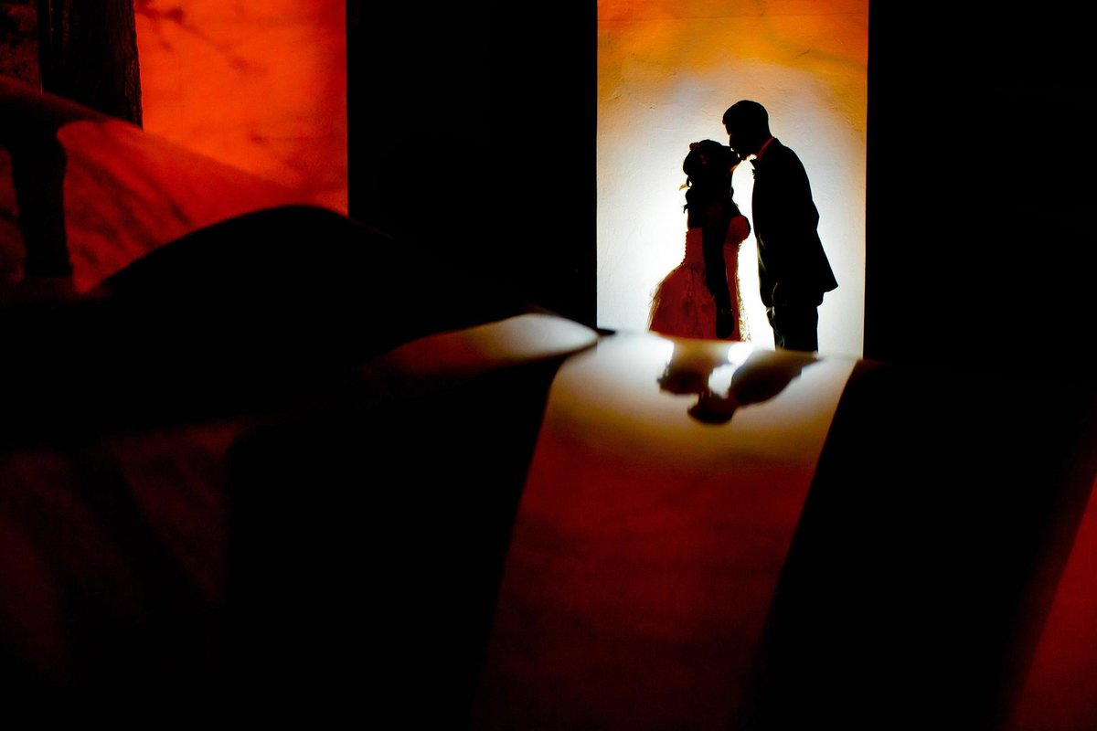 A couple kisses in silhouette at their wedding at Carnivale.