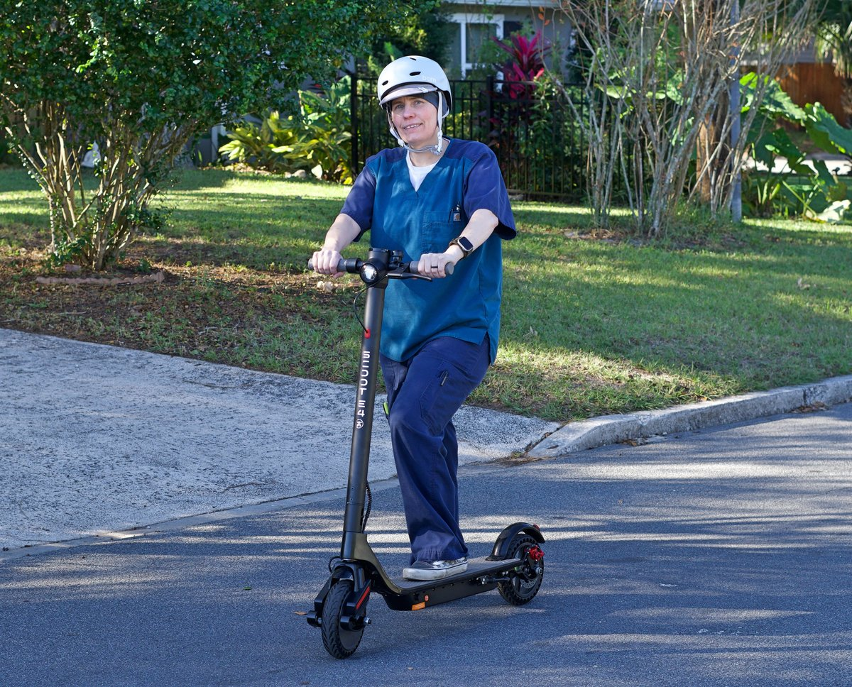 Lady with helmet on Scoot E-4