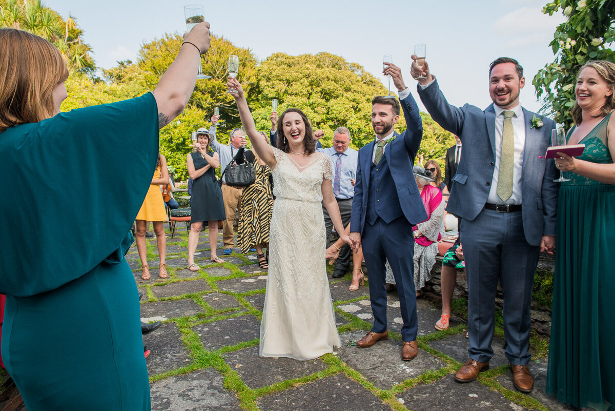 bride in vintage, beaded wedding dress with groom in blue suit toasting with their guests on the terrace of Westcove House, Kerry