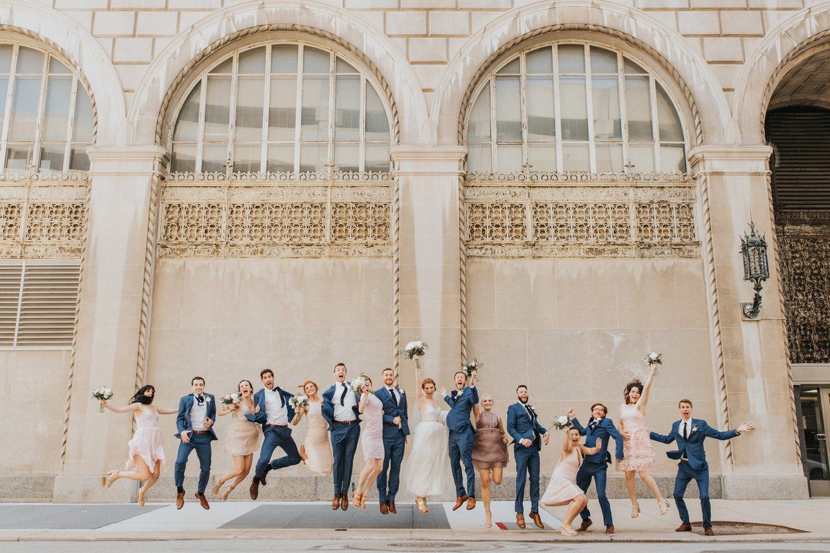 A wedding party jumps for joy in the heart of the city
