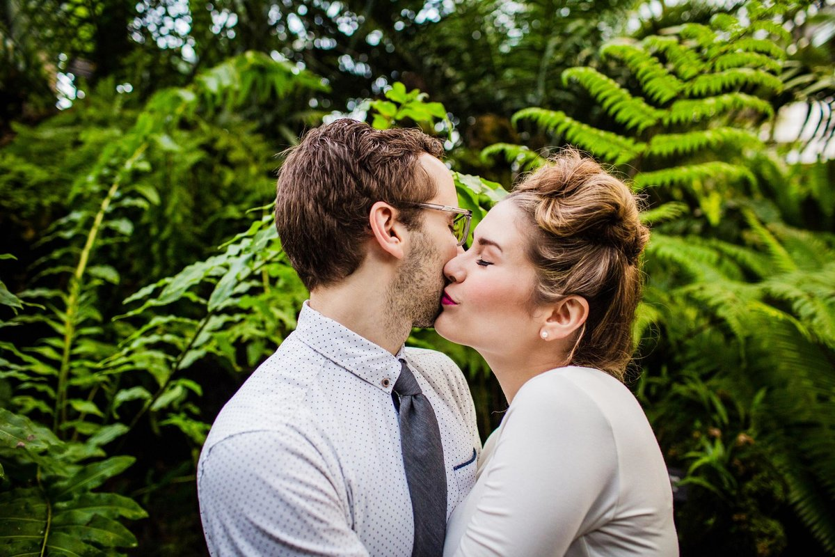 A couple kisses during a Lincoln Park Conservatory engagement session.