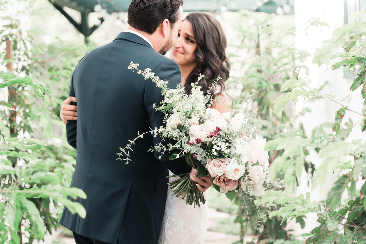 a picture of the bride and groom doing their first look in a garden in Las Vegas