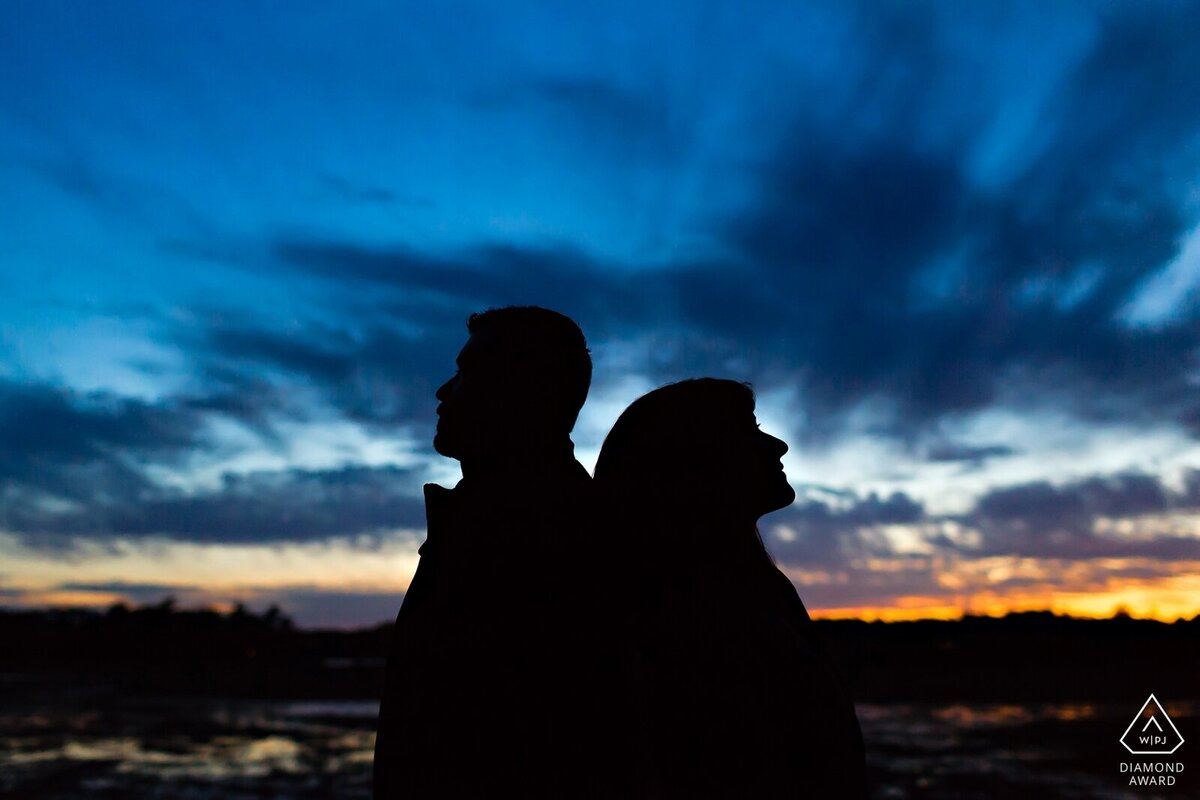 Portsmouth New Hampshire Engagement Session with the couple silhouetted against the sunsetting sky