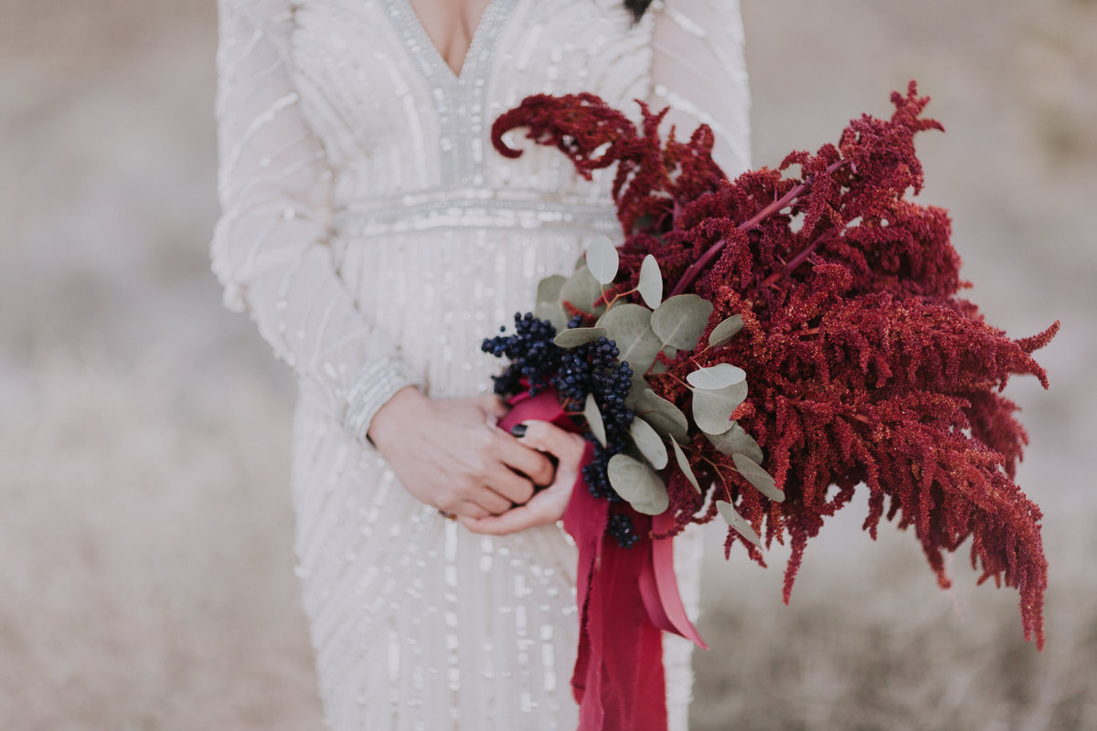 Lake tahoe elopement photographers bride holds her burgundy floral bouquet