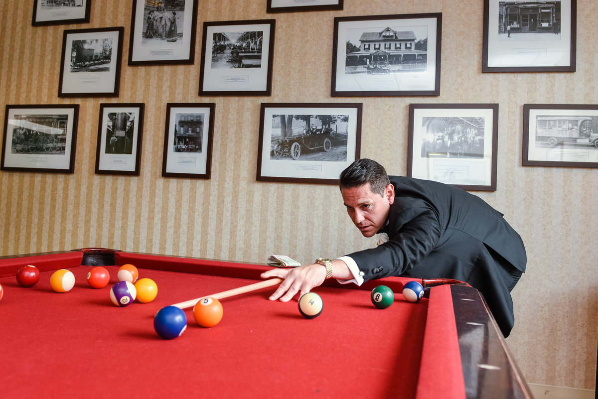 Groom playing pool at Glen Cove Mansion