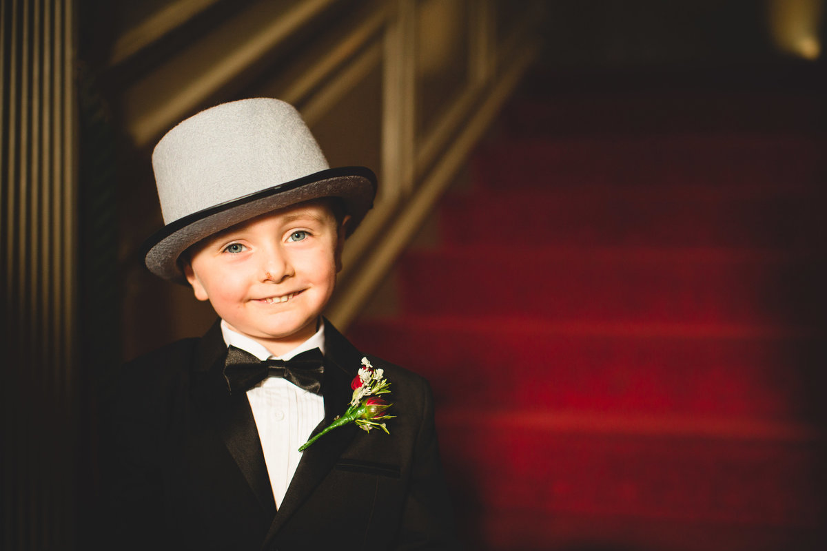 page boy with top hat and bow tie smiling at camera in thornton manor