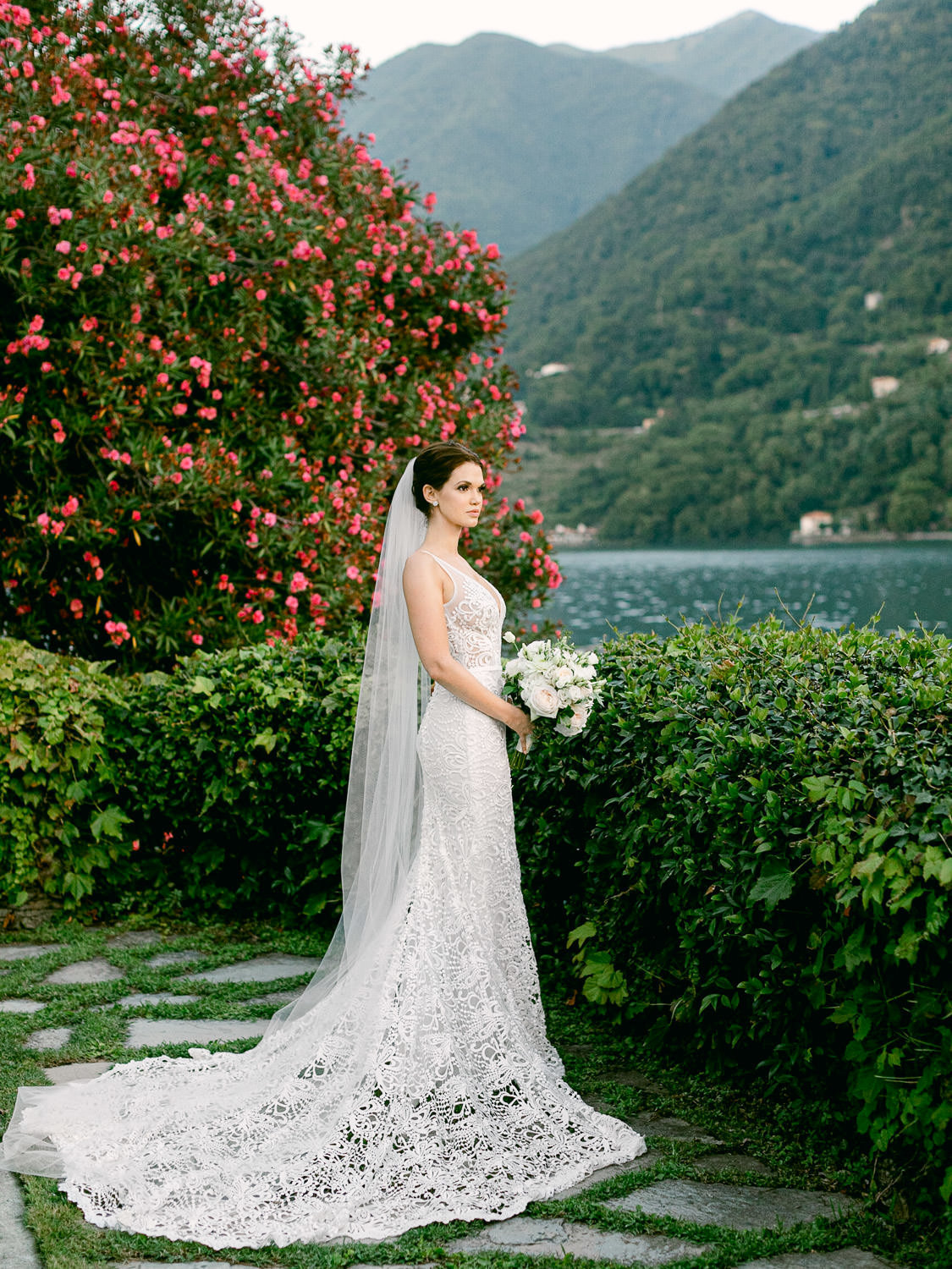 Bride in wedding dress holding bouquet standing by lake Como shore