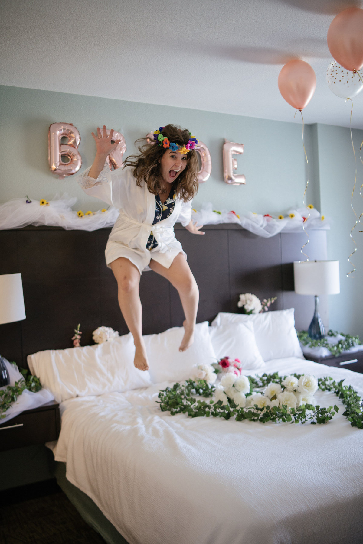 Bride jumping on bed while getting ready for wedding ceremony in downtown San Antonio