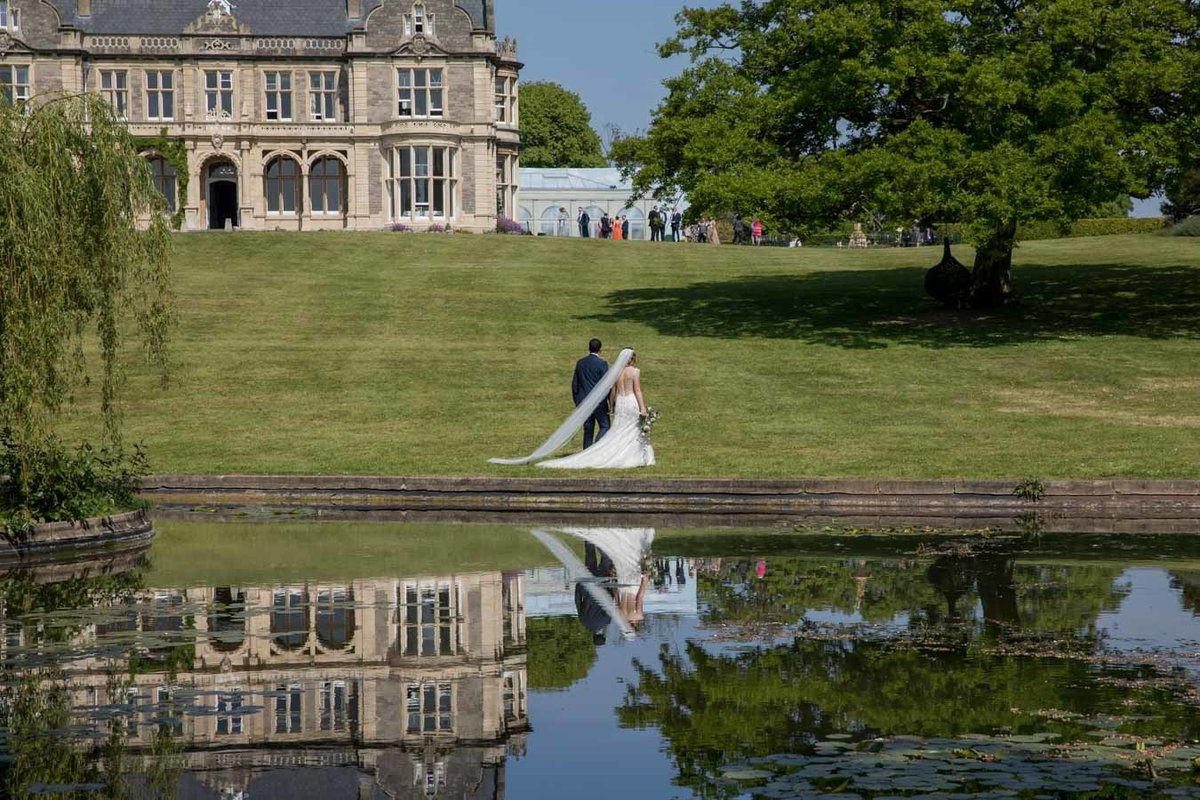 Couple reflected in the pond at Clevedon Hall Somerset