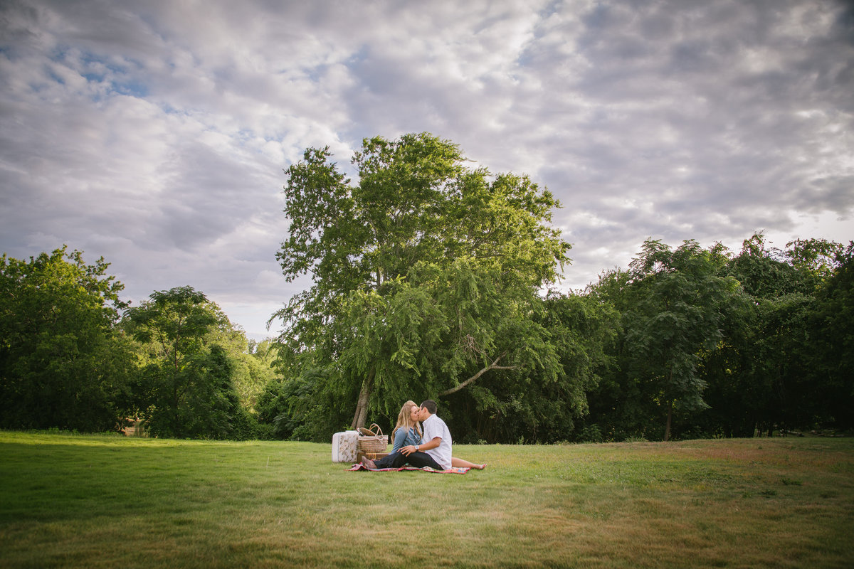 Engaged couple sitting and having a picnic in an open field with a lot of clouds in the sky in Boerne.a