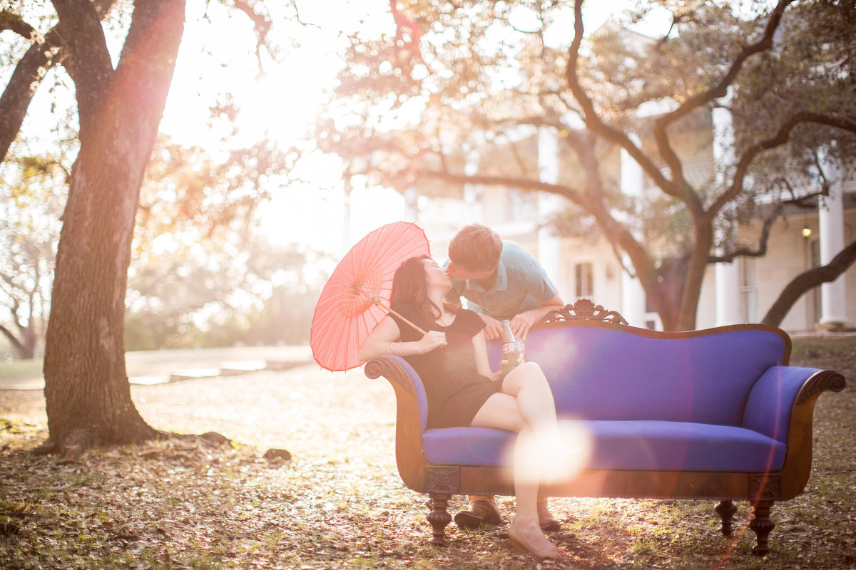 Engagement photography session of couple on a couch kissing with sunlight coming through the trees at Denman Estate Park in San Antonio, Texas.