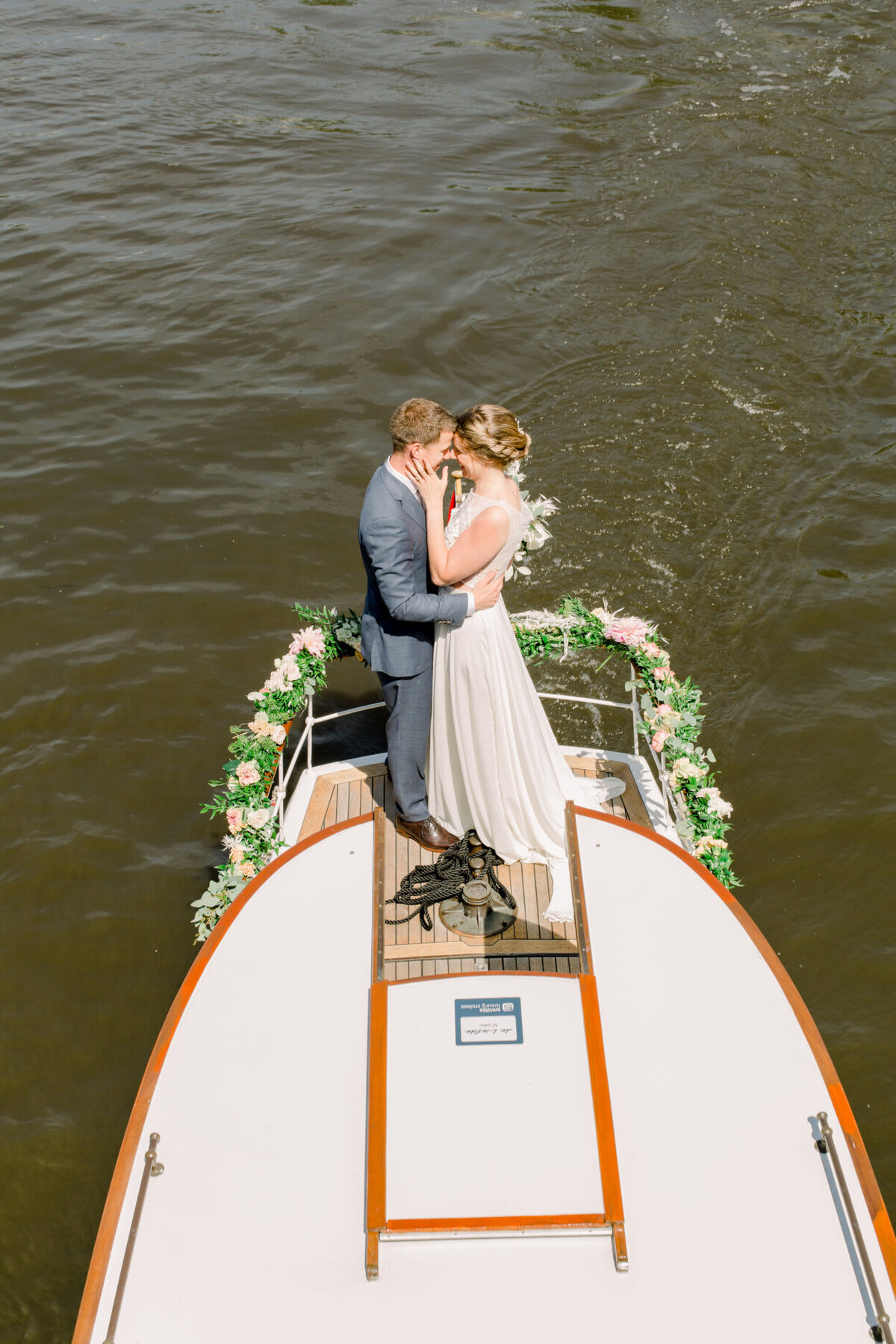 Wedding couple on a canal boat tour in Amsterdam for a photo shoot organized by Lovely & Planned