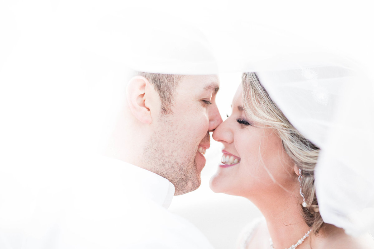 Couple almost kiss under veil at their wedding