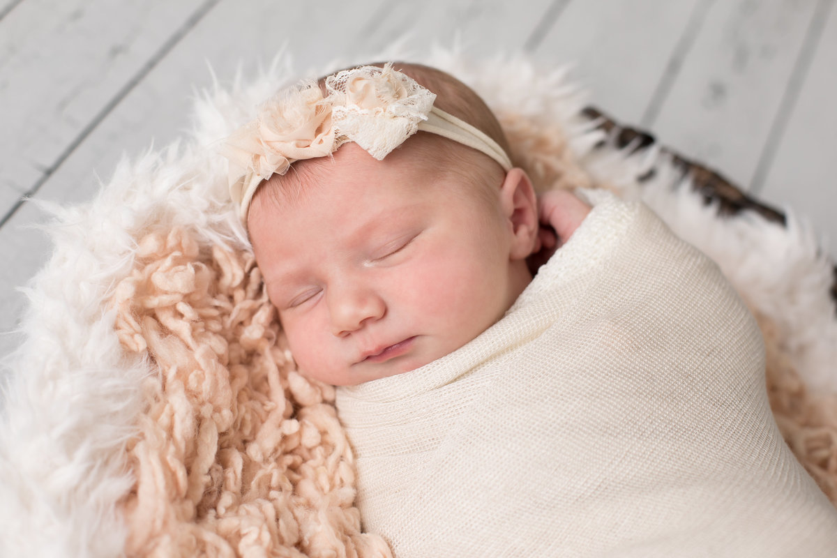 Baby girl in peach wrap and flower headband sleeping in a basket