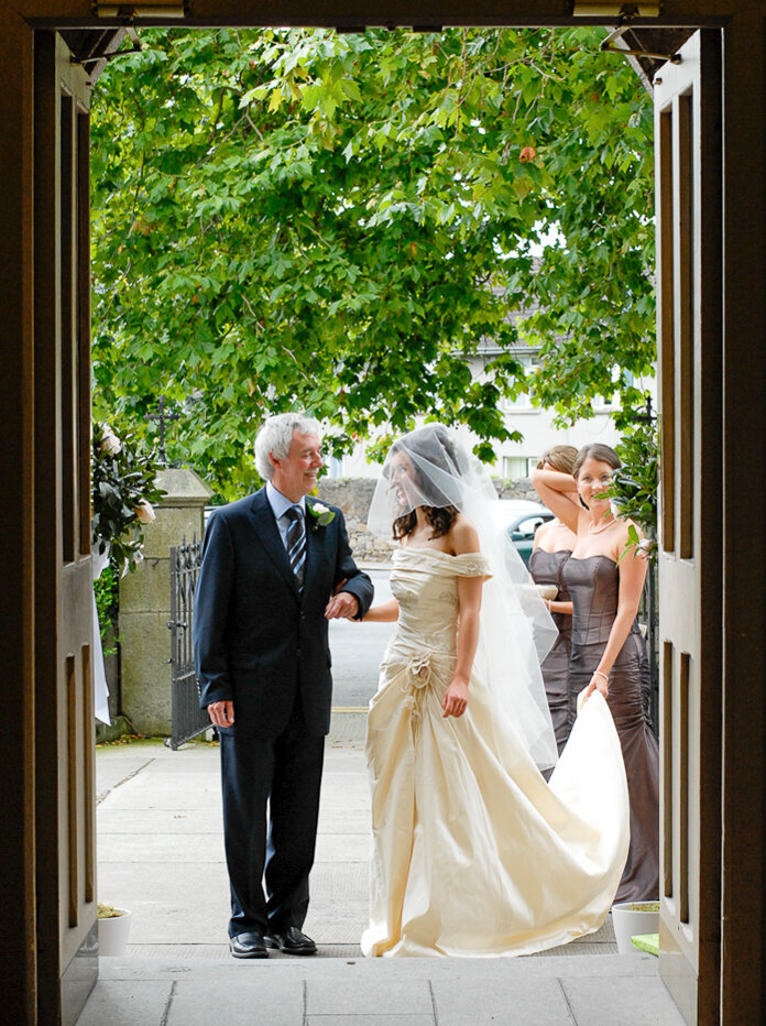 bride wearing a warm ivory, raw silk, a-line wedding dress looking at her father before walking up the aisle
