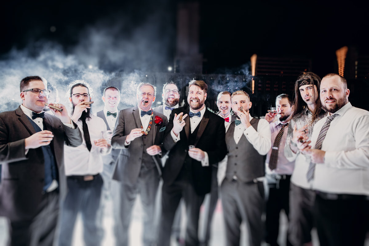 reno wedding photographers groom smoking cigar with groomsmen