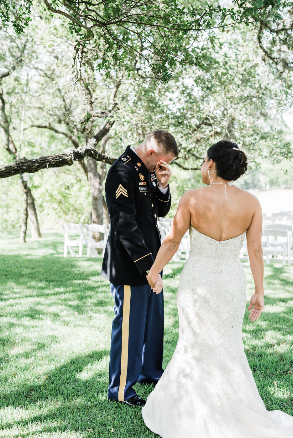 Military groom wiping tear after seeing bride