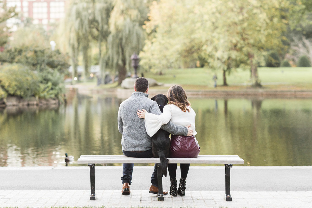 Couple and their dog sitting on a bench in the Boston Public Garden