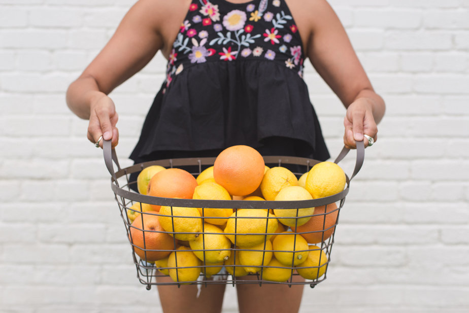 girl holding metal basket with oranges and grapefruits