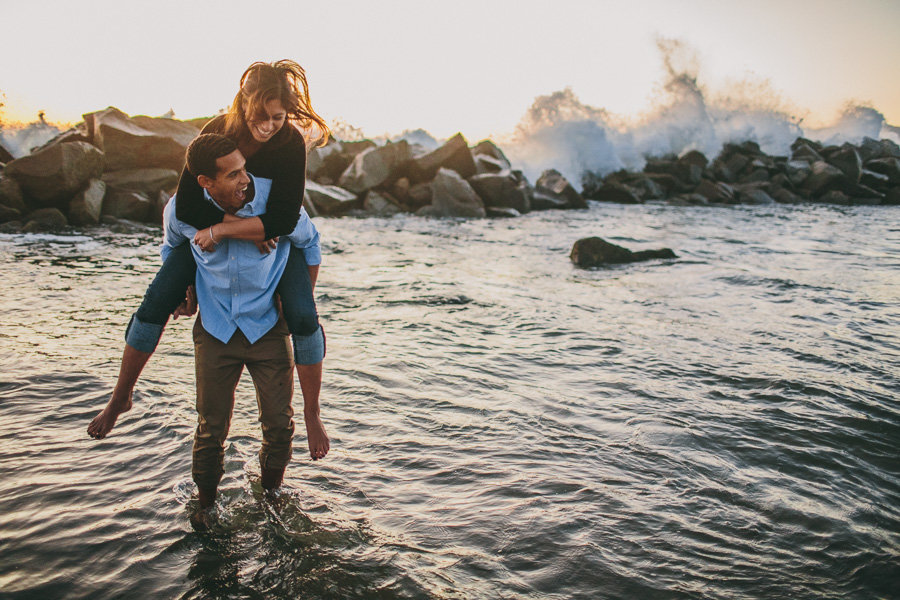 Couple tries to escpape the oncoming wave during their engagement shoot in Newport Beach, Ca.