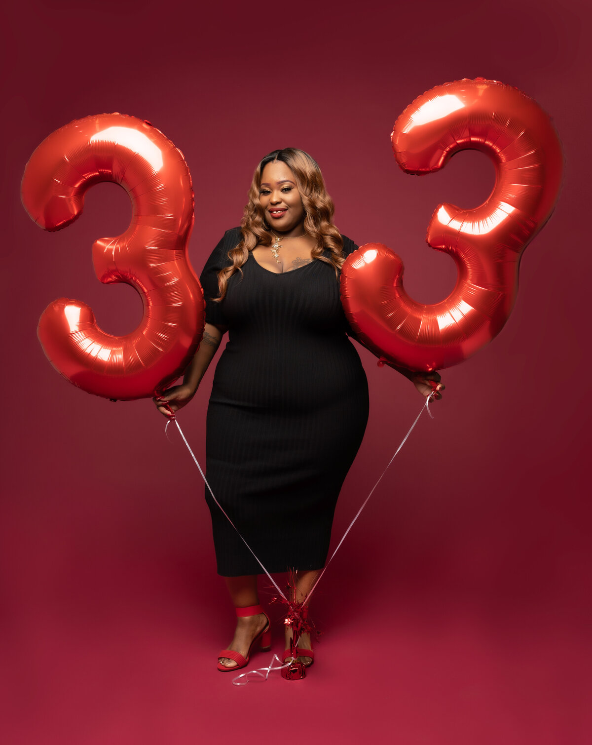 Curvy Black woman in black dress with birthday balloons