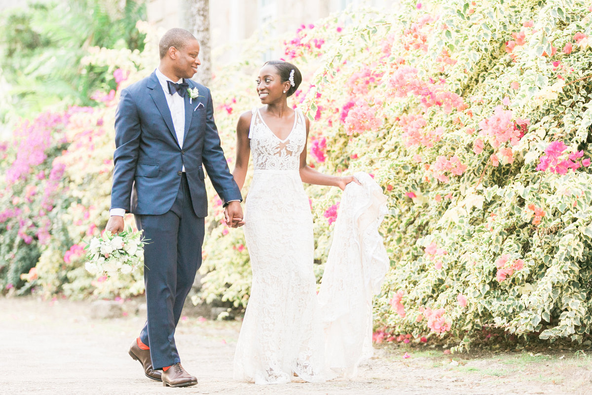Bride and groom taking a stroll after their destination wedding in Barbados, Codrington College