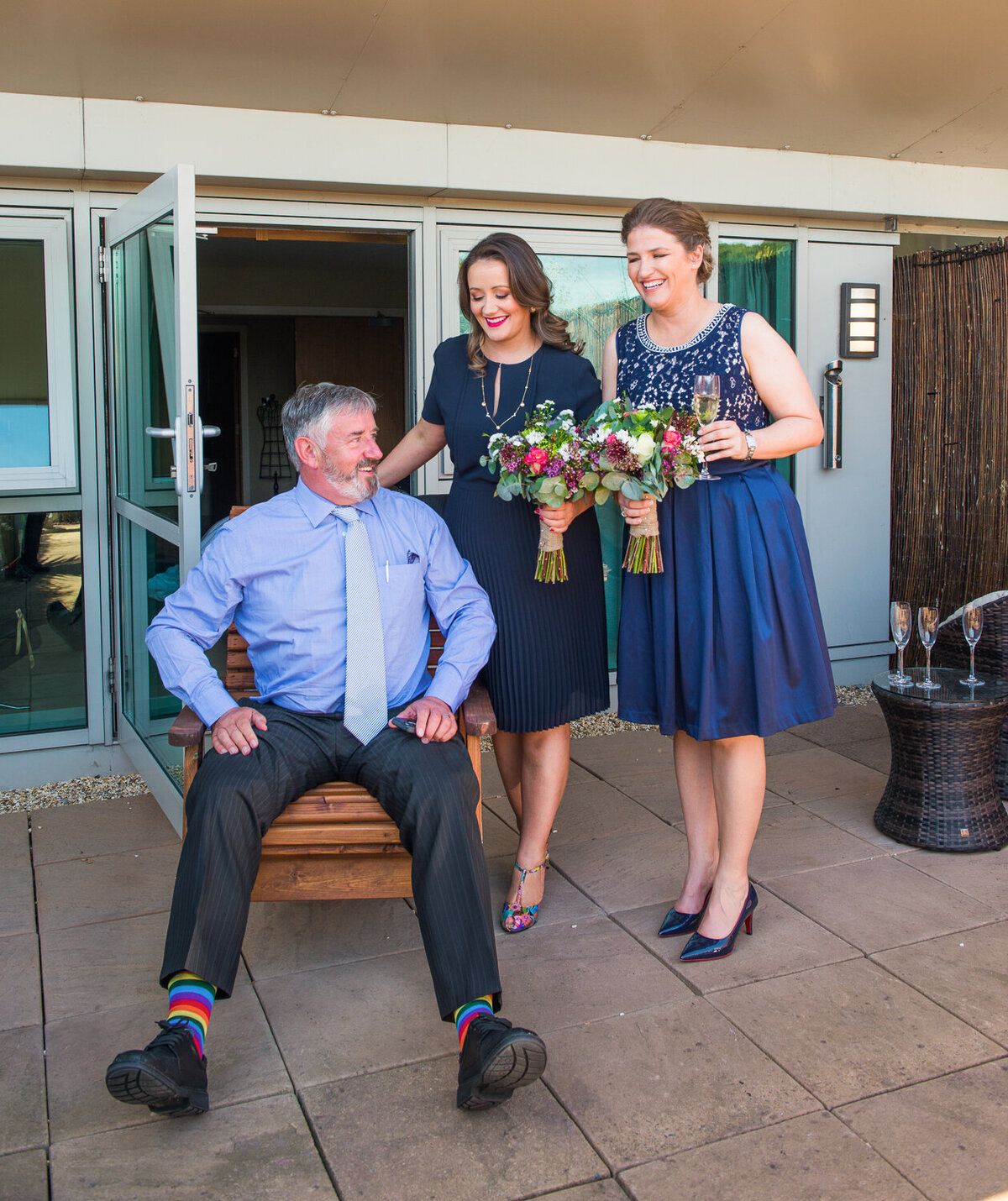 Two brides looking at dad's rainbow socks