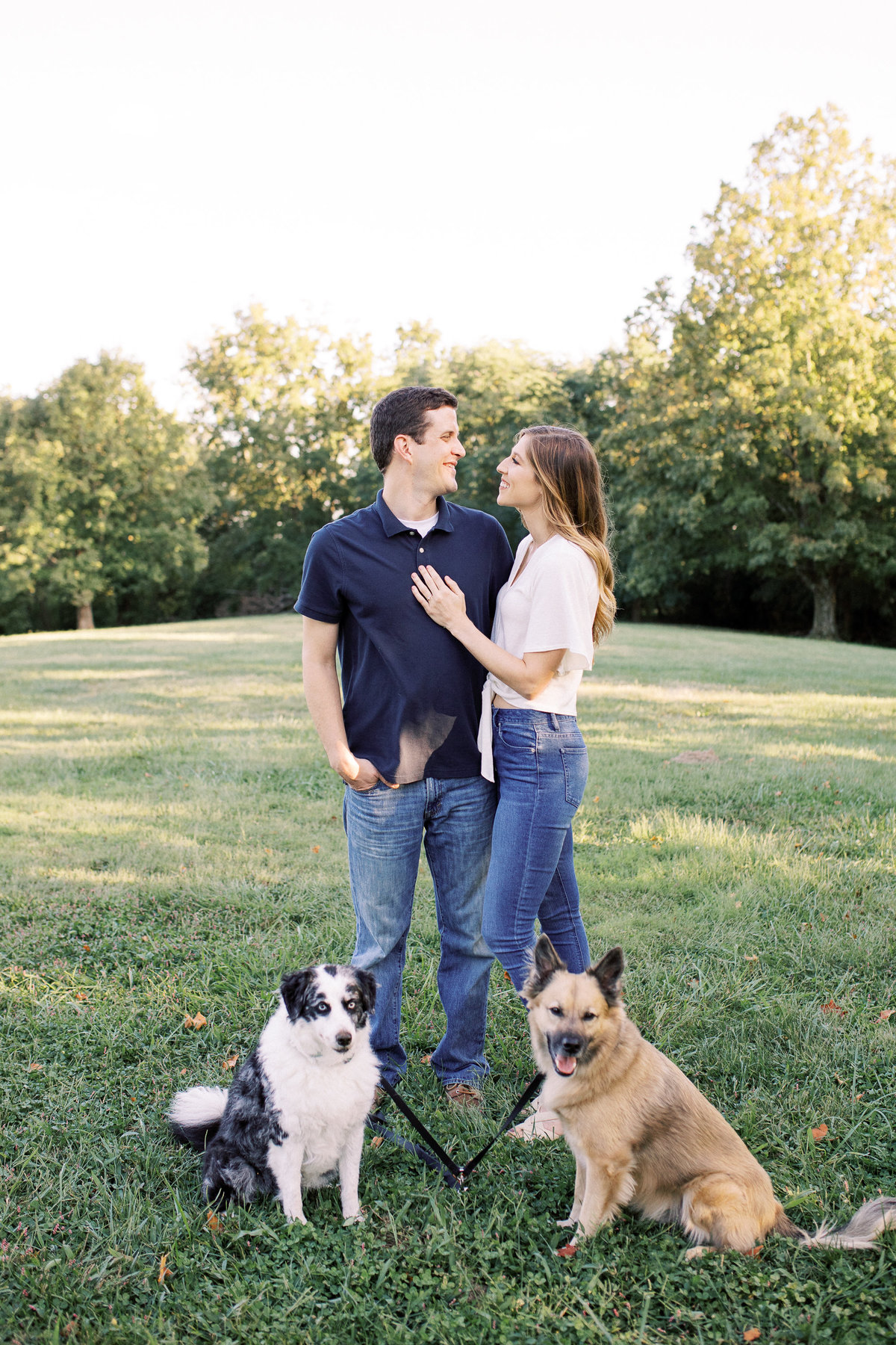 Summer engagement session where a couple stands and looks towards each other in a field as their dogs sit beside them.