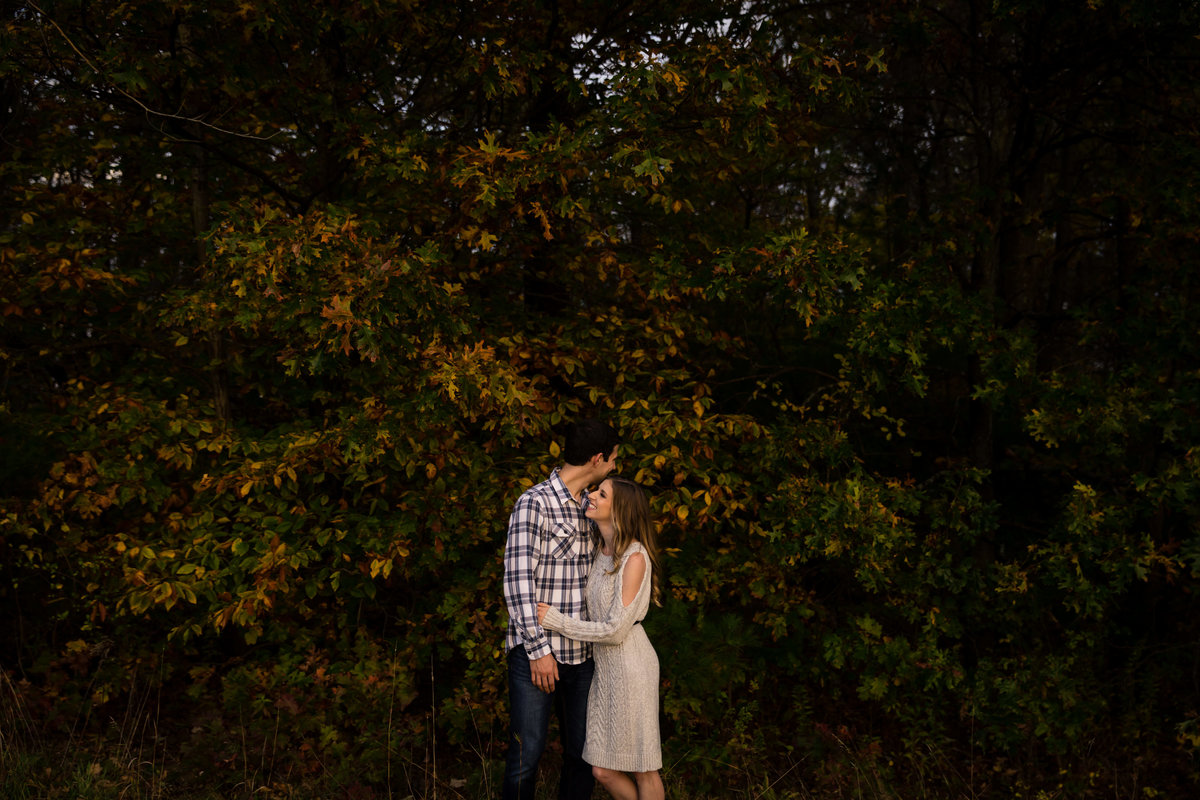 Fall trees and kisses fill this image at the The Preserve at Chocorua NH engagement session