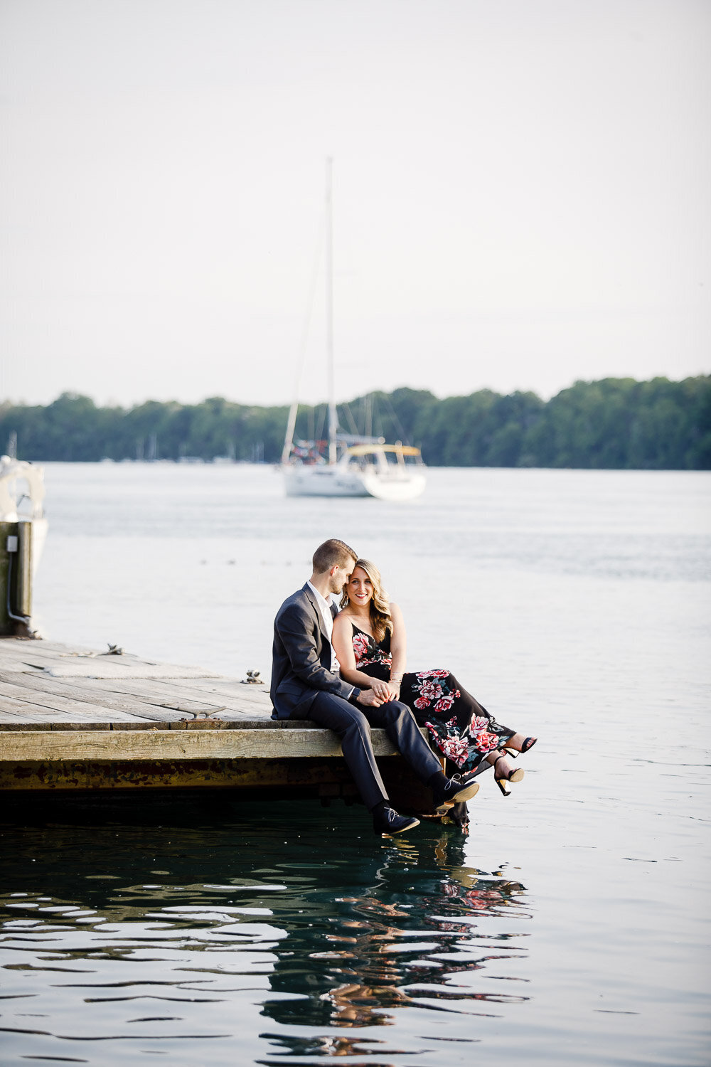 Engaged couple sitting on dock on harbour