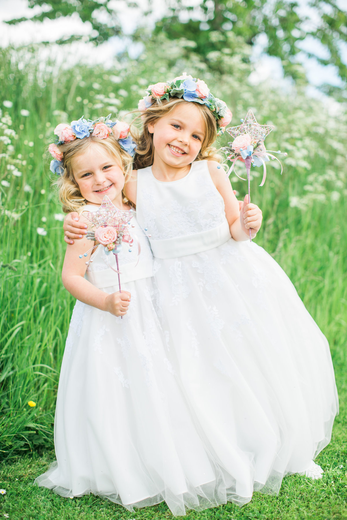 2 flower girls in white dresses with floral headress crowns and wands