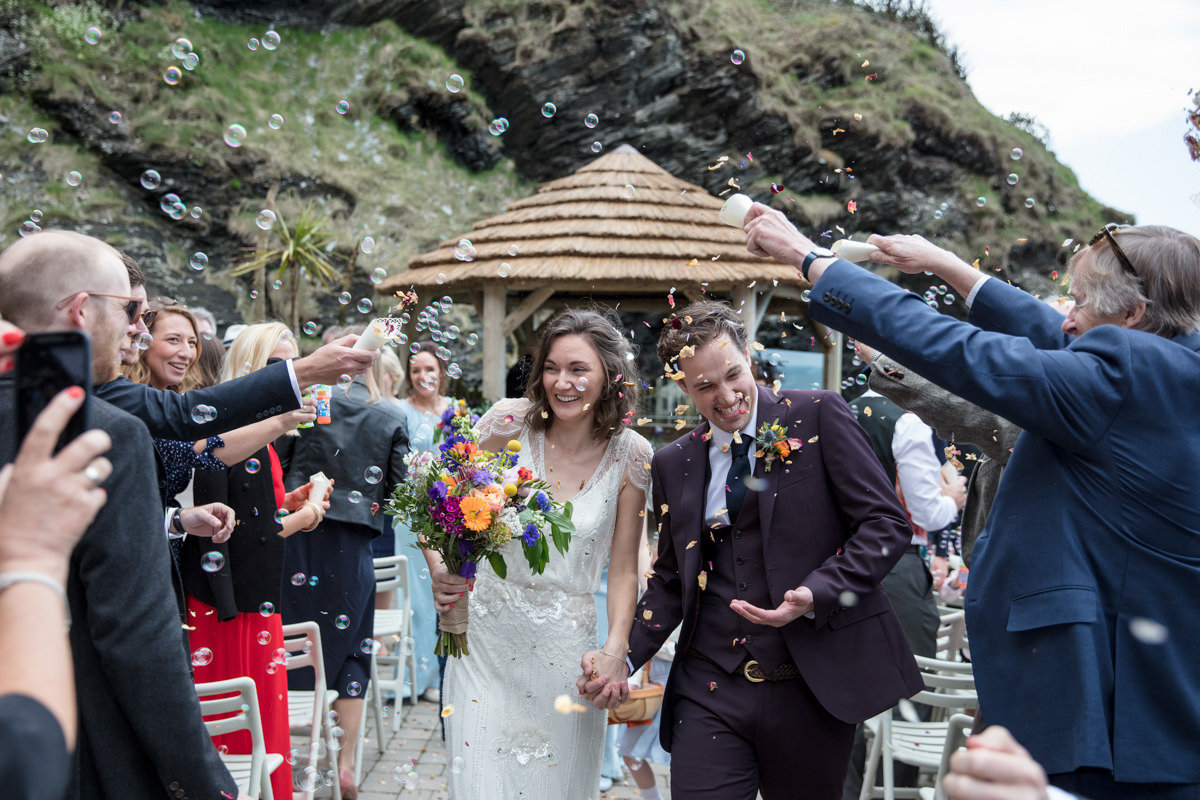 Walking down the aisle with confetti at Tunnels Beaches Devon