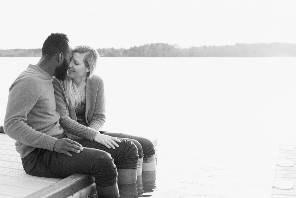 couple sitting on dock at lake