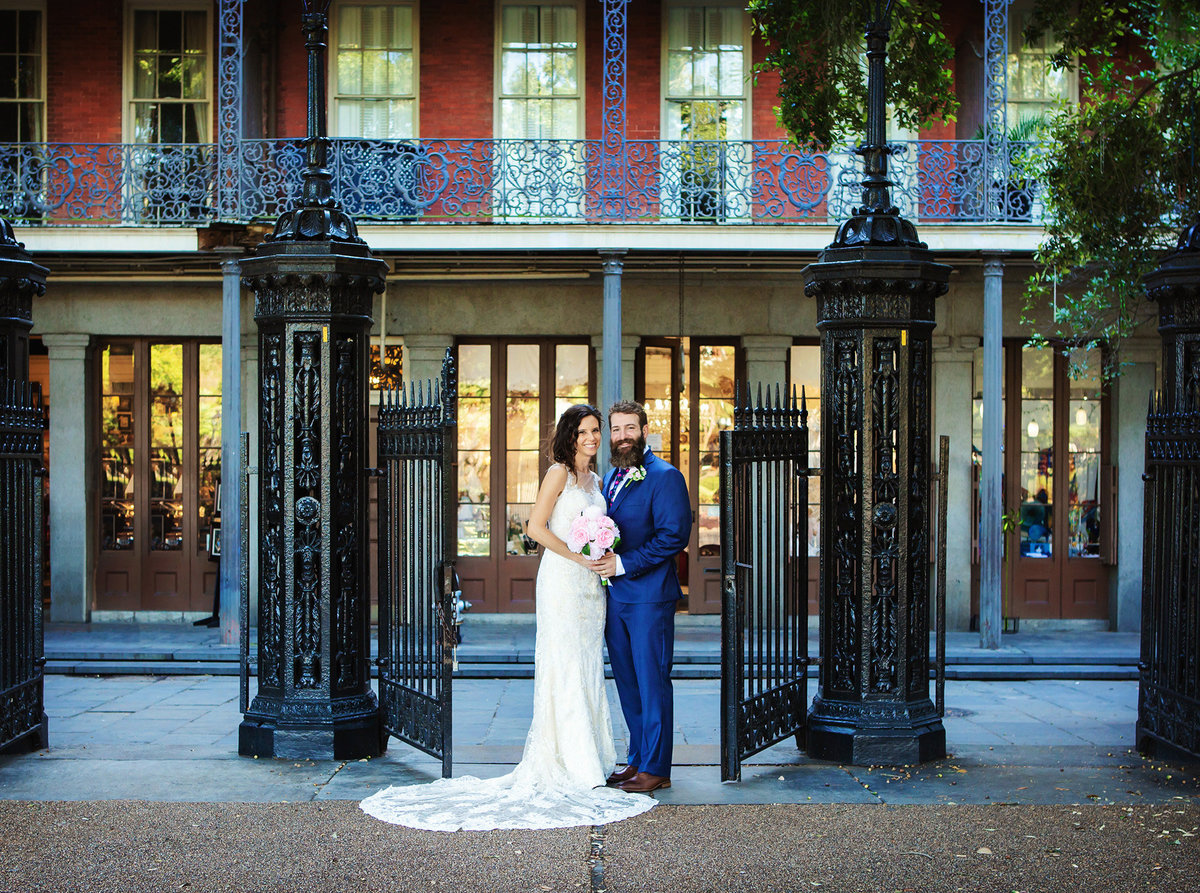 bride and groom at the gates of Jackson Square