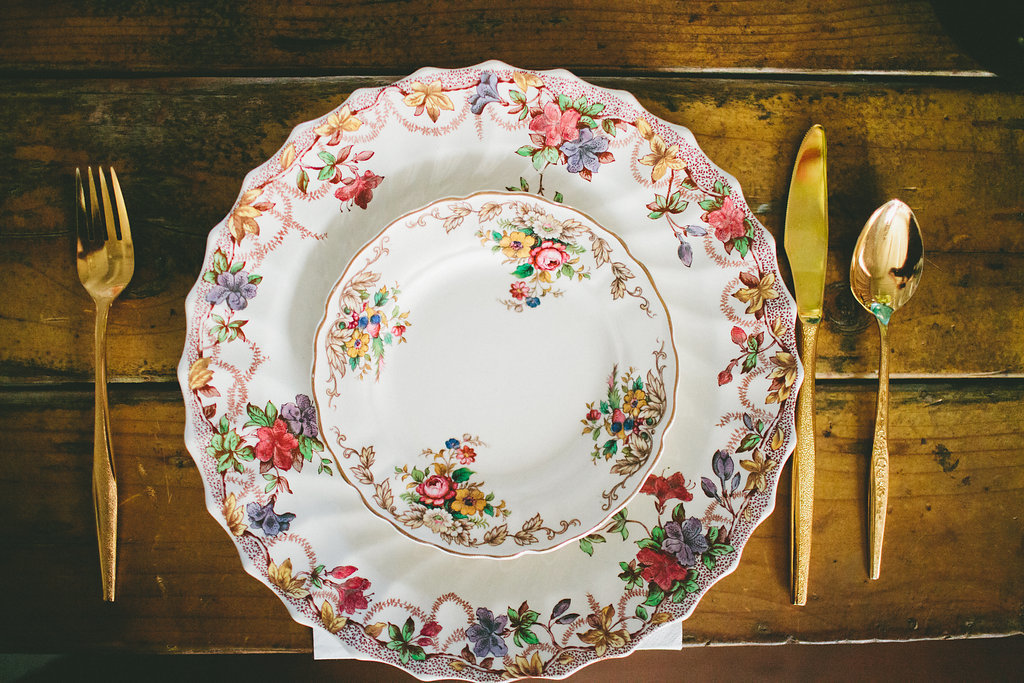 Vintage plate and gold cutlery for dinner party table setting