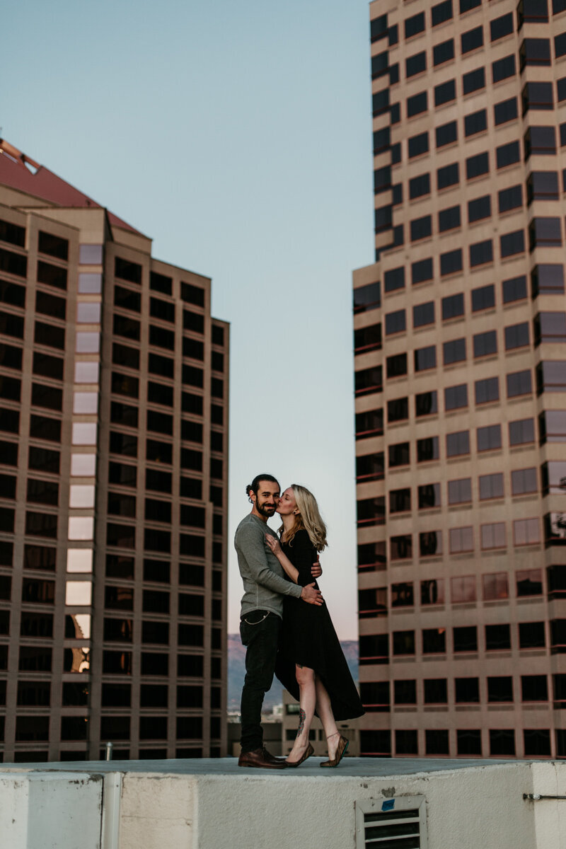 couple kissing on rooftop downtown Albuquerque