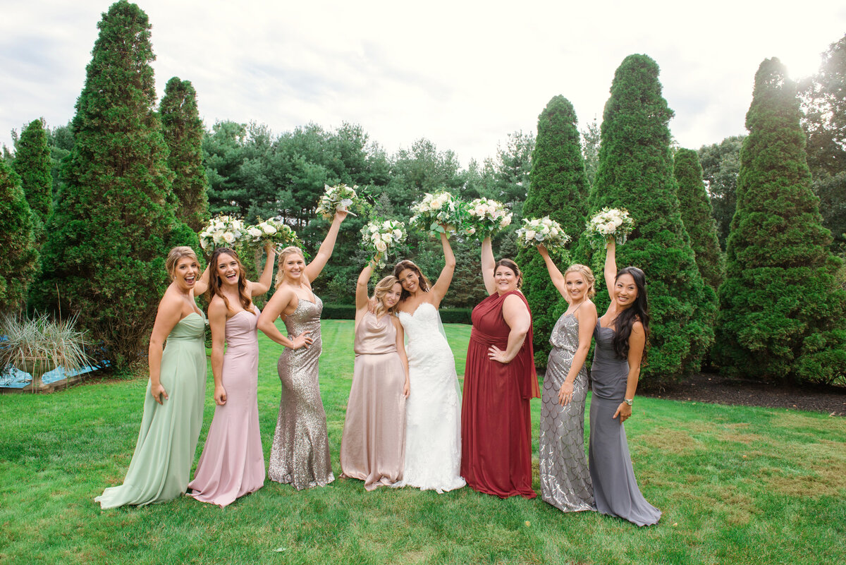 photo of bridesmaids holding their bouquets in the air with bride from wedding at The Carltun