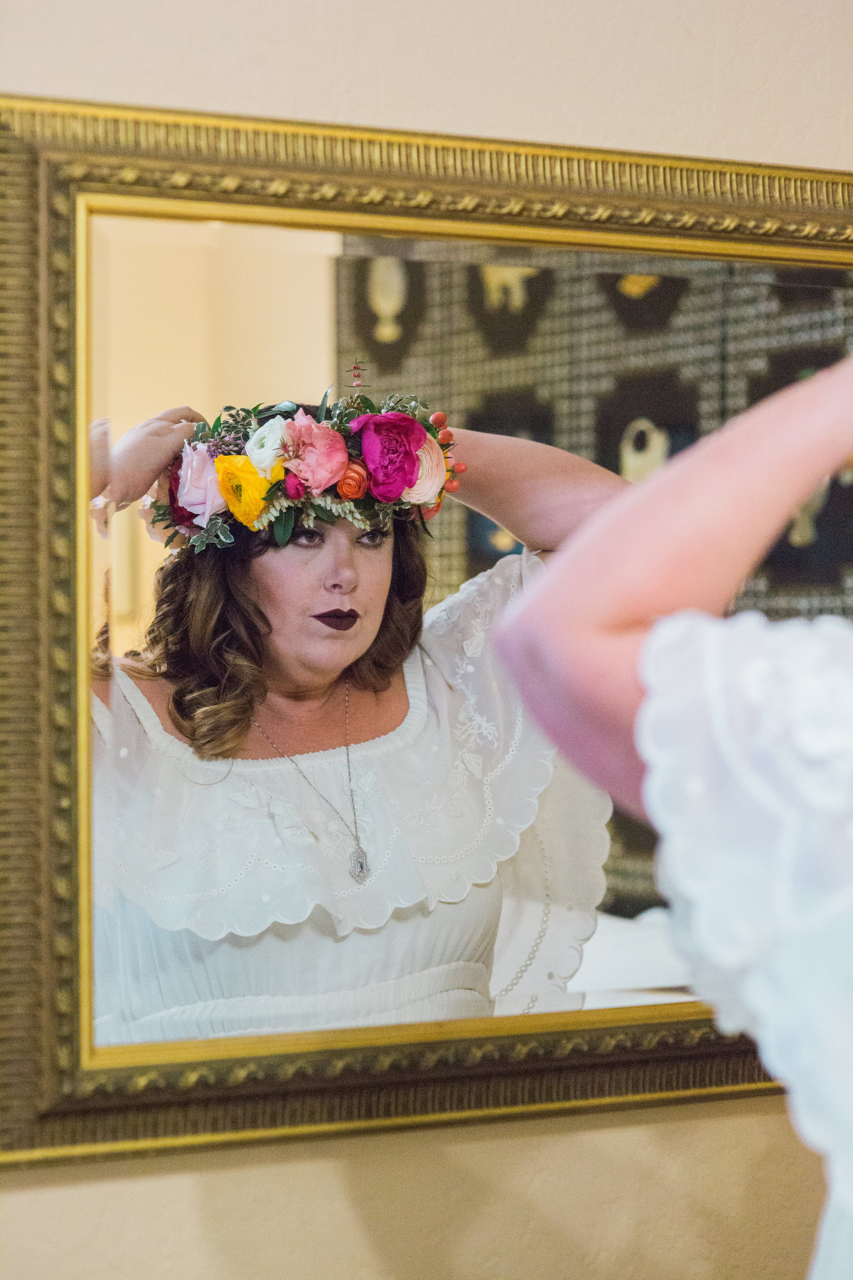 Bride putting on floral crown made my Mack Floral Design in bridal suite at Madrona Manor in Healdsburg California